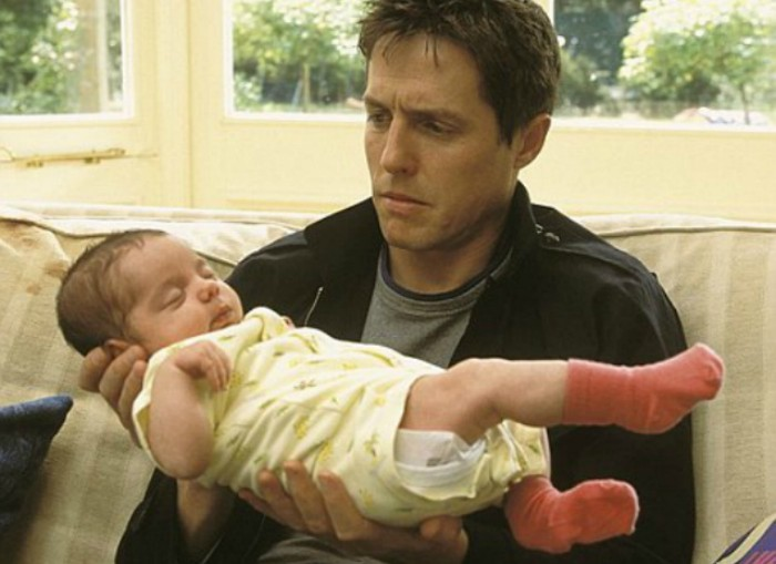 A picture of a man awkwardly holding a baby